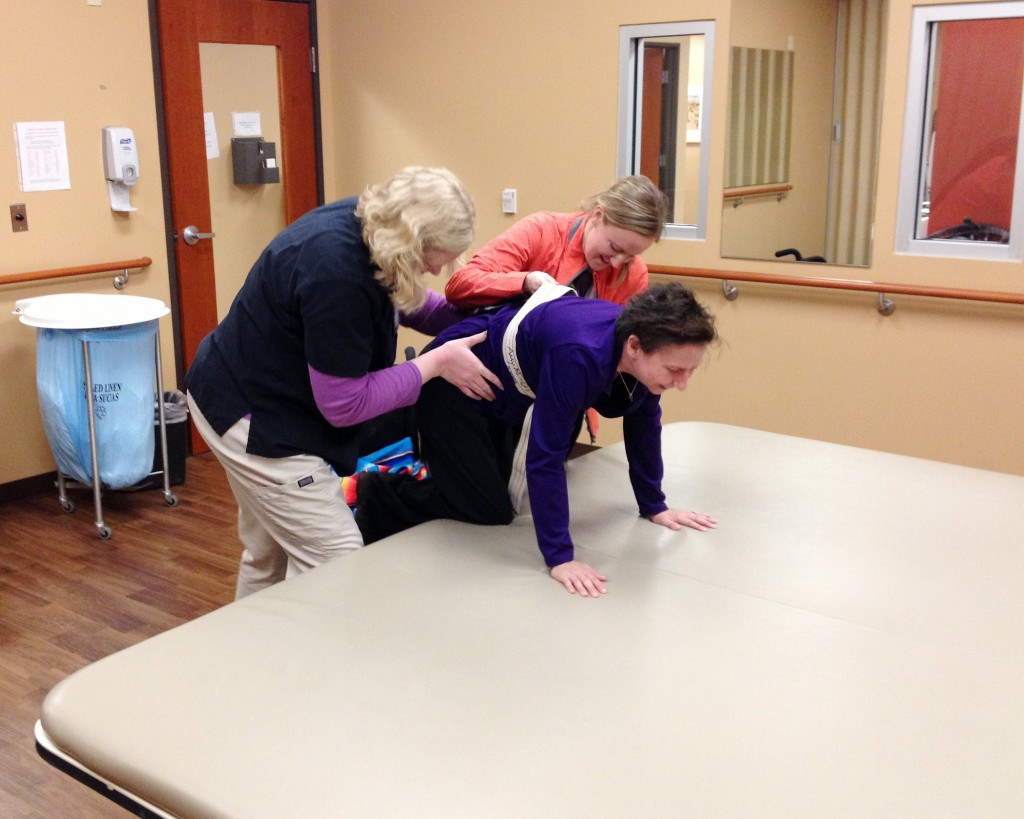 Denise had to crawl on all fours the first time she was able to get out of her wheel chair. Helping here were occupational therapist, Allie Covert and physical therapist, Lanni Boyum. (Photo courtesy John Capelli.)