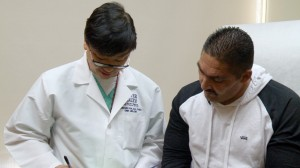 Dr. Fernando Kim, left, a urologist at Denver Health Medical Center meets with Juan Falcon, 49, of Aurora, on March 11, 2015 in Denver before a biopsy was taken to determine if Falcon had prostate cancer. Falcon went to Denver Health after the clinic that originally treated him could not set a follow-up appointment with University Hospital in Aurora. (Mary MacCarthy/Rocky Mountain PBS I-News)