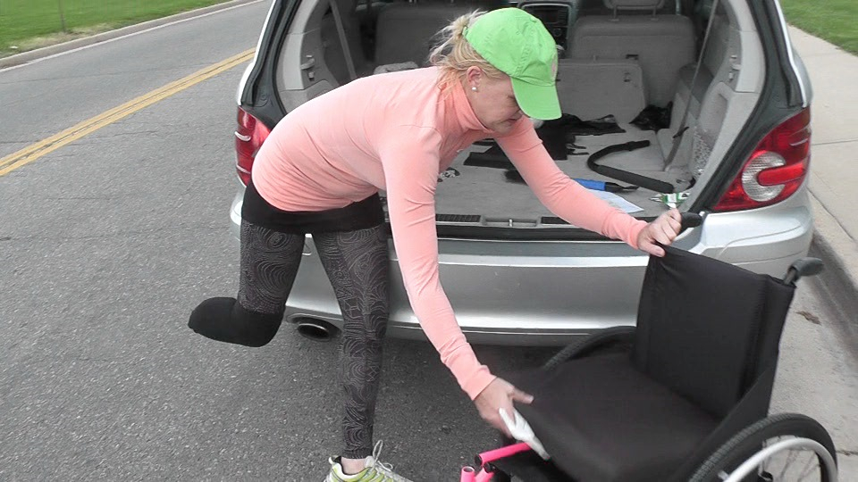Jessica Peck pulls her wheel chair out of her car as she picks her girls up from school.