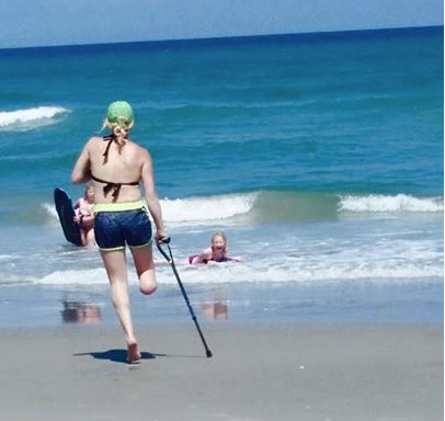 Jessica Peck and her girls took a beach vacation soon after her amputation. She has head to learn to get around with canes and her new bright pink wheel chair.
